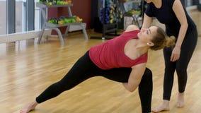 A mulher bonita é ioga das práticas sob a supervisão do treinador no clube desportivo video estoque