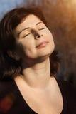 A mulher bonita é relaxar exterior com olhos fechados fotos de stock