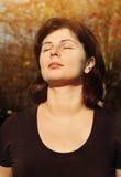 A mulher bonita é relaxar exterior com olhos fechados imagem de stock
