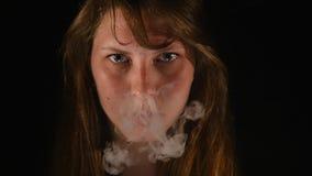 A mulher bonita épico fuma o cigarro eletrônico e e faz o isolado das nuvens de fumo no preto, adolescente vaping, e-cig e video estoque