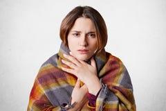 A mulher bonita adorável sente congelada, coberto na manta morna, isolada sobre o fundo concreto branco O modelo fêmea tem o frio foto de stock