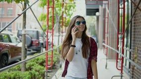 A mulher bonita alegre em vidros à moda e no equipamento na moda tem a conversa telefônica e dar uma volta na rua video estoque