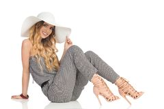 A mulher bonita alegre no fato-macaco, no chapéu de Sun e nos saltos altos está sentando-se no assoalho fotos de stock
