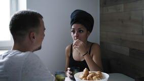 Mulher bonita após o chuveiro com a toalha escura em sua cabeça que come croissant e que bebe o café Fala a seu noivo video estoque