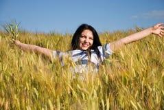 A mulher bonita aprecia o verão no campo de trigo Fotos de Stock Royalty Free