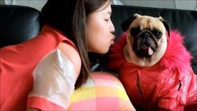 Mulher bonita asiática nova que funde um beijo a seu cão do pug no sofá vídeos de arquivo