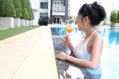 Mulher bonita asiática nova que relaxa na piscina Fotos de Stock