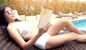 Mulher bonita asiática nova que relaxa na piscina que encontra-se na Foto de Stock