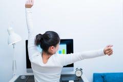 A mulher bonita asiática nova que senta-se na frente do computador e estica-se oneself após o trabalho longo stree-livre e relaxe fotografia de stock royalty free