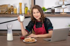 Mulher bonita asiática que guarda um vidro do leite foto de stock