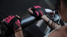 A mulher bonita atlética executa na extensão do pé do simulador filme