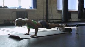 A mulher bonita atlética faz Impulso-UPS como parte de sua aptidão transversal, rotina do treinamento do Gym do halterofilismo video estoque
