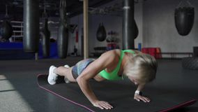 A mulher bonita atlética faz Impulso-UPS como parte de sua aptidão transversal, rotina do treinamento do Gym do halterofilismo filme