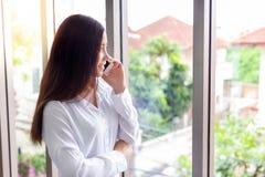 A mulher bonita atrativa está chamando a sua família de ultramarino foto de stock