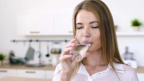 A mulher bonita bebe a água de um copo de vidro na manhã video estoque