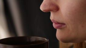 A mulher bonita bebe o café ou o chá que olham para fora a janela Movimento lento video estoque