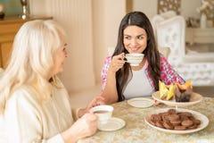 A mulher bonita bebe o chá com sua mãe superior no café imagens de stock royalty free