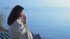 A mulher bonita bebe o chá envolvido em uma manta e em olhares no nascer do sol que senta-se no banco de rio video estoque