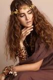 Mulher bonita Cabelo longo encaracolado Modelo de forma no vestido dourado Penteado ondulado saudável acessórios Autumn Wreath, c fotos de stock