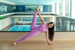 Mulher bonita calma nova que veste o sportswear lilás que dá certo o aga fotografia de stock royalty free