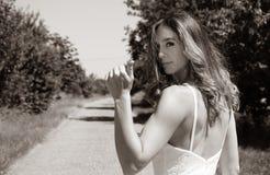 Mulher bonita, caroneiro da noiva nos polegares brancos do vestido para um elevador em uma estrada secundária ao mostrar seu pé foto de stock
