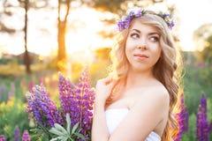 Mulher bonita cercada pelo campo de flores Imagens de Stock