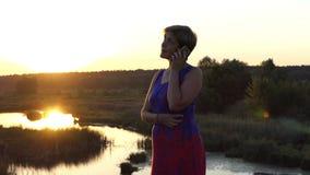 A mulher bonita chama em um por do sol esplêndido no verão video estoque
