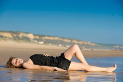 A mulher bonita colocou no snad na praia Imagens de Stock