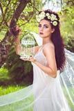 Mulher bonita com as flores naturais no cabelo e no birdcage Fotos de Stock Royalty Free