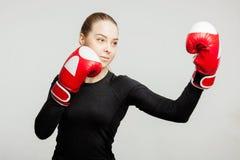 A mulher bonita com as luvas de encaixotamento vermelhas bate o treinamento fêmea atrativo do pugilista do apercote fotos de stock
