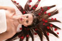 Mulher bonita com as pétalas vermelhas da flor Foto de Stock