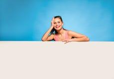 Mulher bonita com auriculares sobre um painel vazio Imagens de Stock