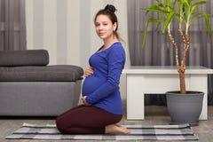 A mulher bonita com barriga inchada, veste a camiseta azul e as caneleiras, poses em joelhos no apartamento moderno, preparam-se  fotos de stock