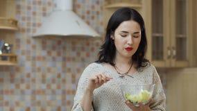 A mulher bonita com bordos vermelhos come a salada fresca vídeos de arquivo