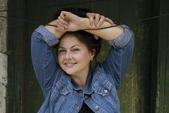 A mulher bonita com cabelo castanho escuro sorri no fundo da madeira do vintage Fotos de Stock Royalty Free