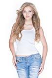 Mulher bonita com cabelo encaracolado longo na calças de ganga fotografia de stock royalty free