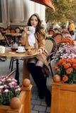 Mulher bonita com cabelo escuro no equipamento elegante que senta-se no café foto de stock royalty free