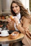 Mulher bonita com cabelo escuro no equipamento elegante que senta-se no café fotografia de stock royalty free
