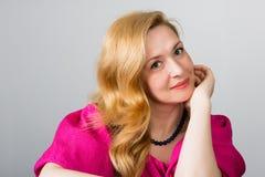 Mulher bonita com cabelo louro em um cinza Fotografia de Stock Royalty Free