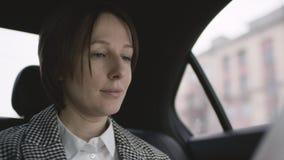 Mulher bonita com cabelo marrom na equitação branca da blusa e do revestimento da verificação em documentos de trabalho do carro  filme