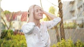 Mulher bonita com cabelo molhado que aprecia a chuva e que olha acima ao céu Mulher bonita no jardim do verão que tem o muito video estoque