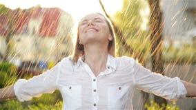 Mulher bonita com cabelo molhado que aprecia a chuva e que olha acima ao c?u Mulher bonita no jardim do ver?o que tem o muito video estoque