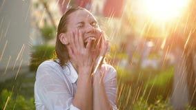 Mulher bonita com cabelo molhado que aprecia a chuva e que olha acima ao c?u Mulher bonita no jardim do ver?o que tem o muito filme