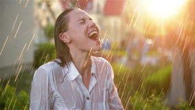 Mulher bonita com cabelo molhado que aprecia a chuva e que olha acima ao c?u Mulher bonita no jardim do ver?o que tem o muito vídeos de arquivo