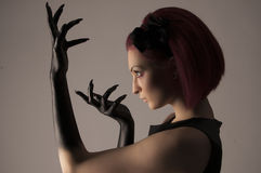 Mulher bonita com cabelo vermelho e pintura preta nas mãos Fotografia de Stock Royalty Free