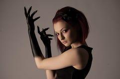 Mulher bonita com cabelo vermelho e pintura preta nas mãos Fotos de Stock Royalty Free