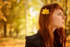 Mulher bonita com cabelo vermelho no parque da queda Fotografia de Stock Royalty Free