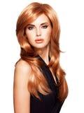 Mulher bonita com cabelo vermelho por muito tempo reto em um vestido preto. fotografia de stock royalty free