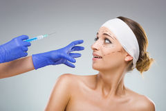 Mulher bonita com cirurgia plástica, o medo da agulha, mãos de um cirurgião plástico Fotos de Stock