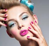 Mulher bonita com composição azul dos olhos e de pregos cor-de-rosa imagem de stock